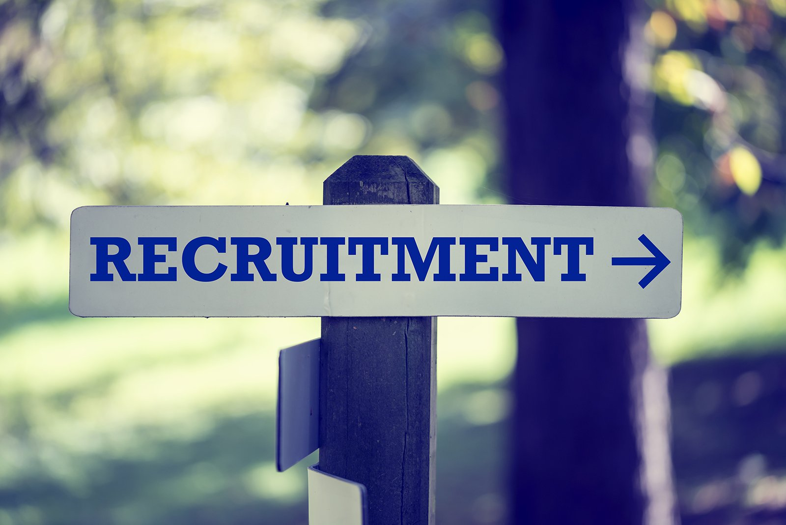 "Two posts outside with signs showing directions. Sign shows the word ""recruitment"" with arrow pointing to the right"