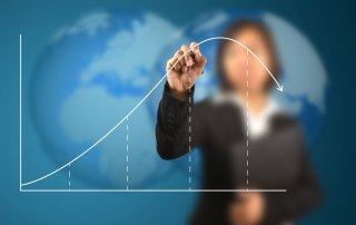 woman drawing line graph of business life cycle on board