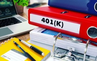 "A yellow notebook with pens lying on the cover. A stack of binders sits next to the notebook. A red binder is marked ""401k"" on the spine"