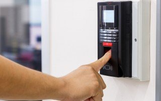 Photo of employee pressing a finger on the pad of a wall-mounted biometric time clock to enter a time punch.