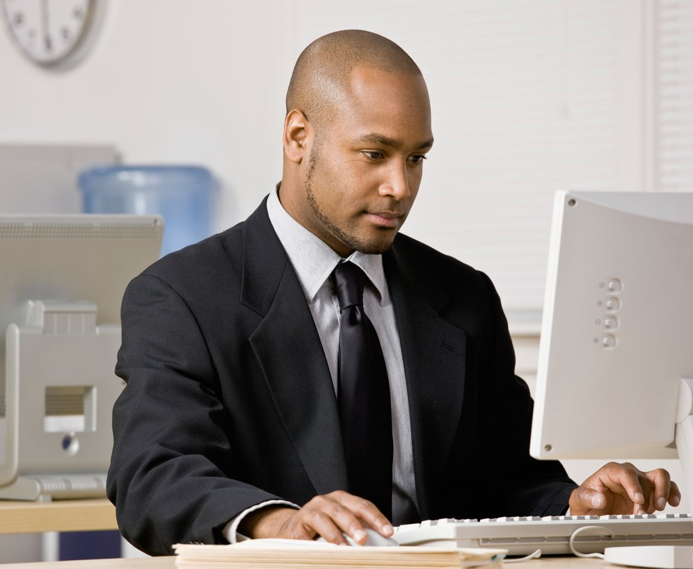 A serious businessman working at his computer in an office