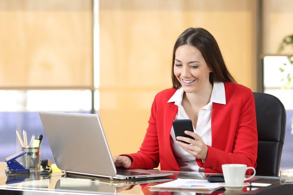 Young business woman using laptop and smartphone