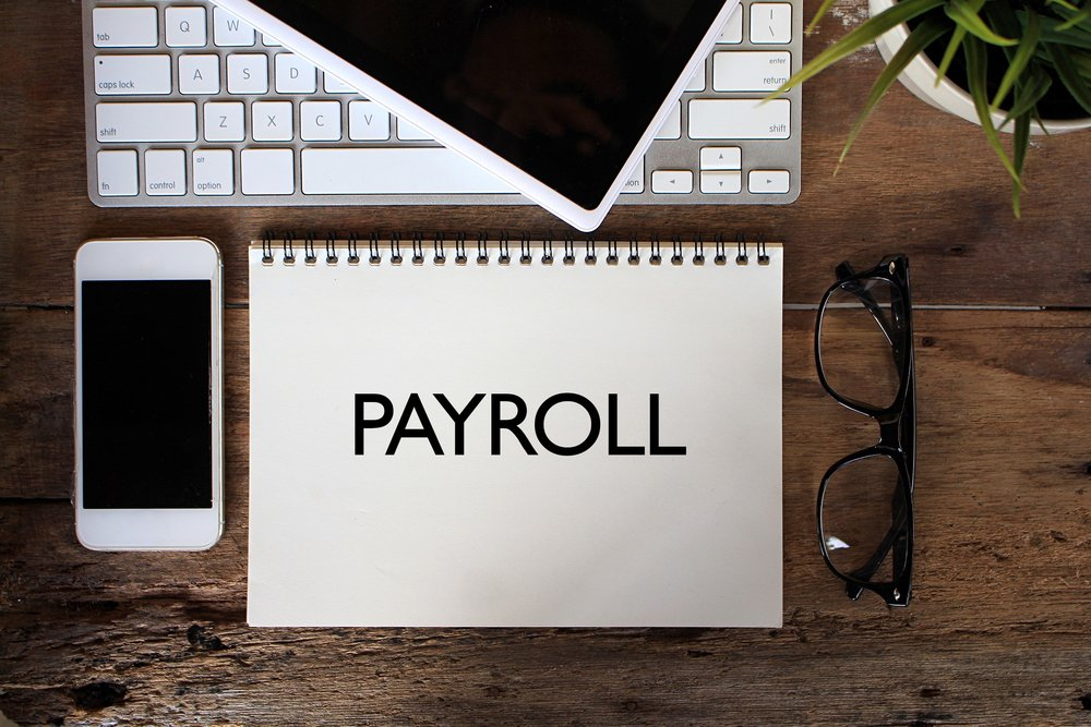 "The word ""Payroll"" written on an open journal sitting on desk with computer, mobile phone, tablet, eye glasses, and a plant"