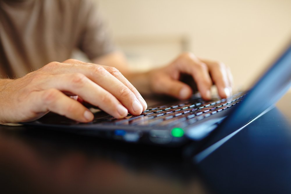 Close-up photo of man's hands on computer keyboard