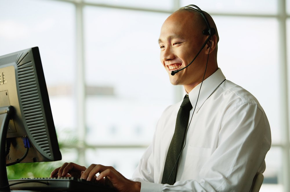 Photo of smiling businessman at desktop computer