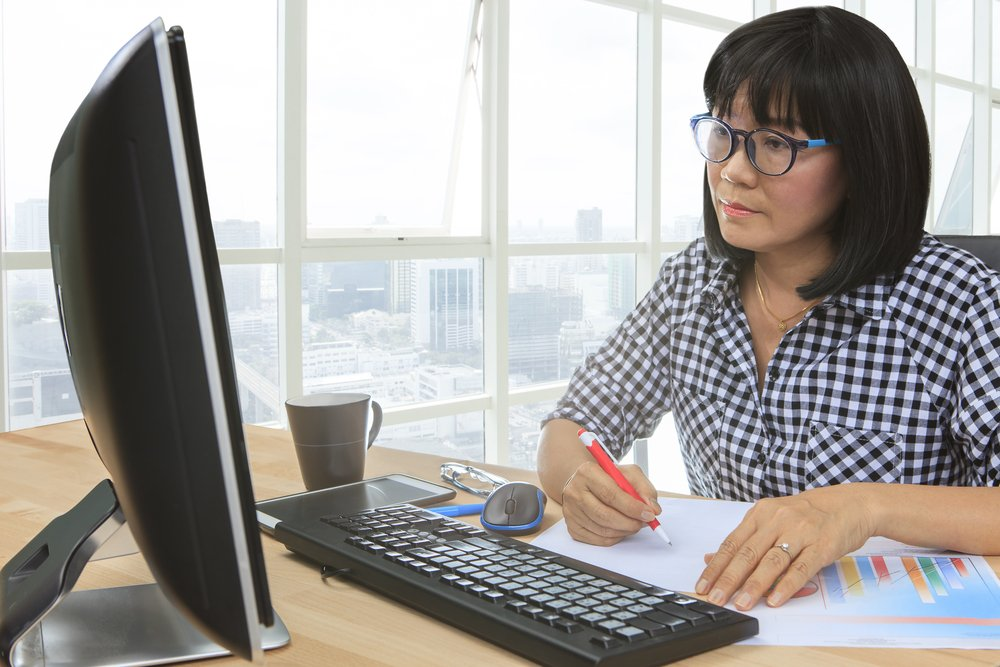 Photo of woman with glasses working at desktop computer