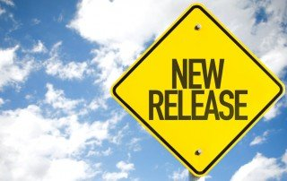 "Yellow diamond-shaped sign with words ""New Release"" held up against cloudy blue sky"