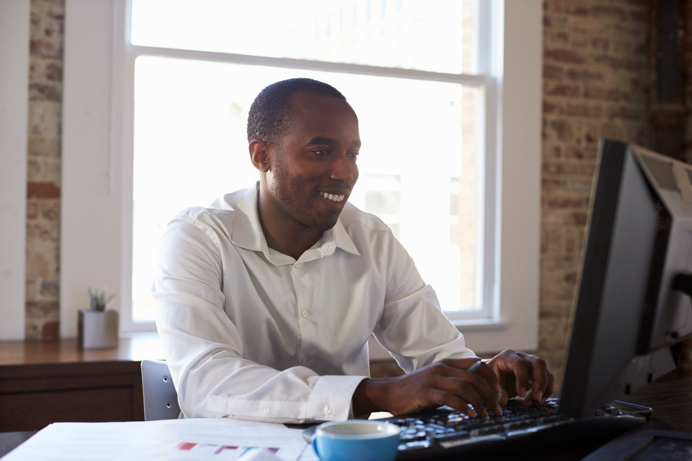 smiling man sitting in office working at laptop