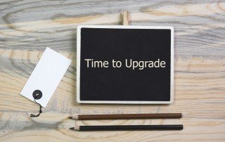 "Chalkboard with the sentence ""Time to Upgrade"" written in white and sitting on a wooden table with black and brown pencils"