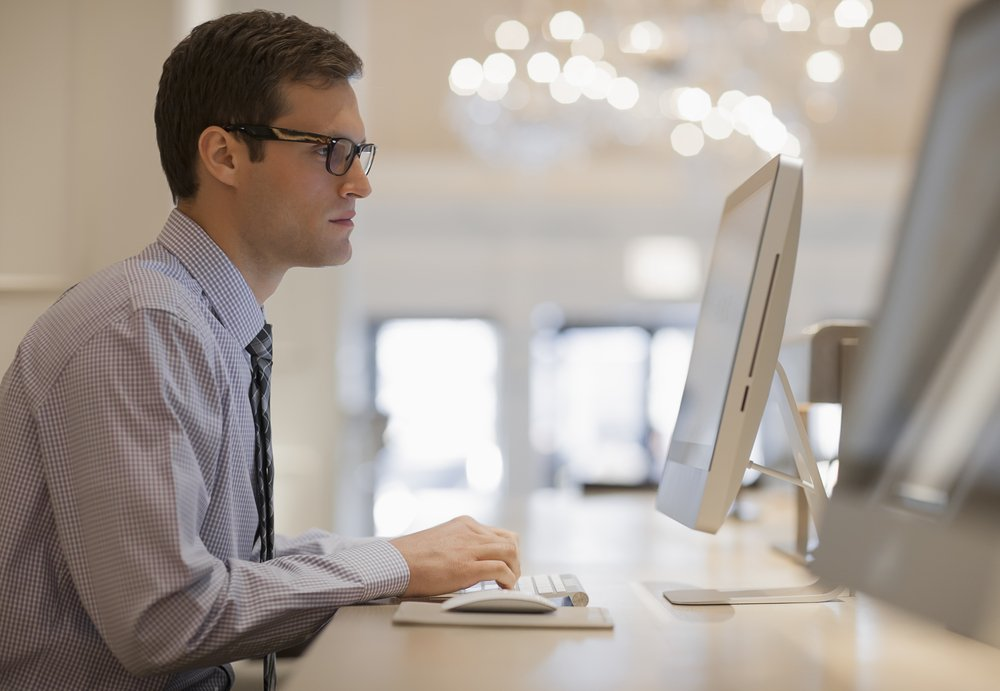 Young man with glasses working at a computer