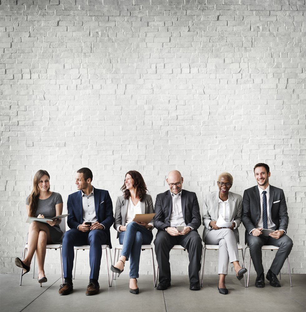 diverse group of job applicants sitting in front of a white brick wall
