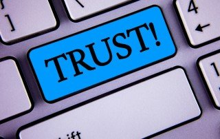 "Close up of sliver computer keyboard with the word ""Trust!"" written on a blue key."