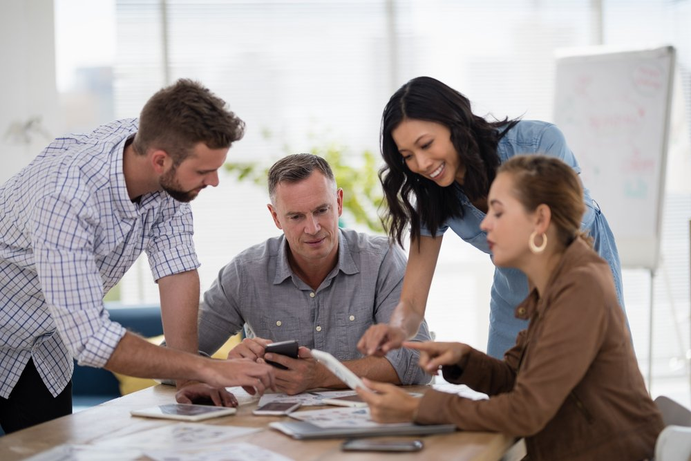 Photo of four employees meeting at a table in their office