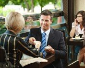 man and woman sitting in a coffee shop exchanging business cards