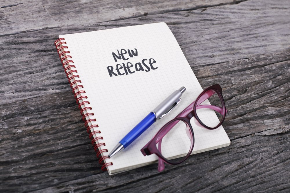 "Photo of notepad with words ""New Release"" written in bold letters. A pen and glasses sit on top of the notepad."