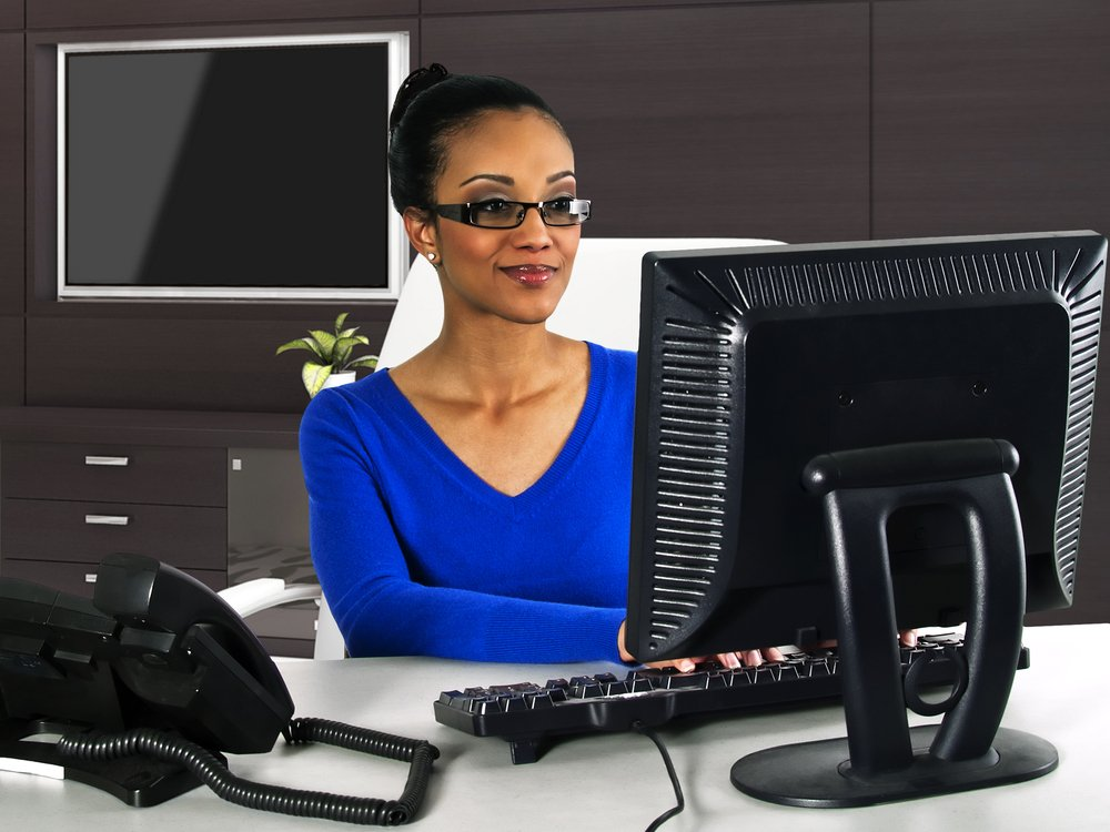 Woman with glasses wearing a blue top as she works at her desktop computer