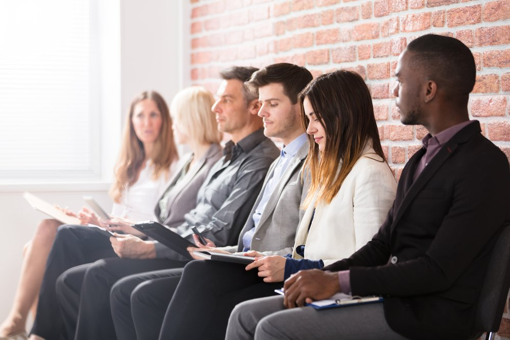 a diverse group of job applicants sitting in a row of chairs in front of a red brick wall