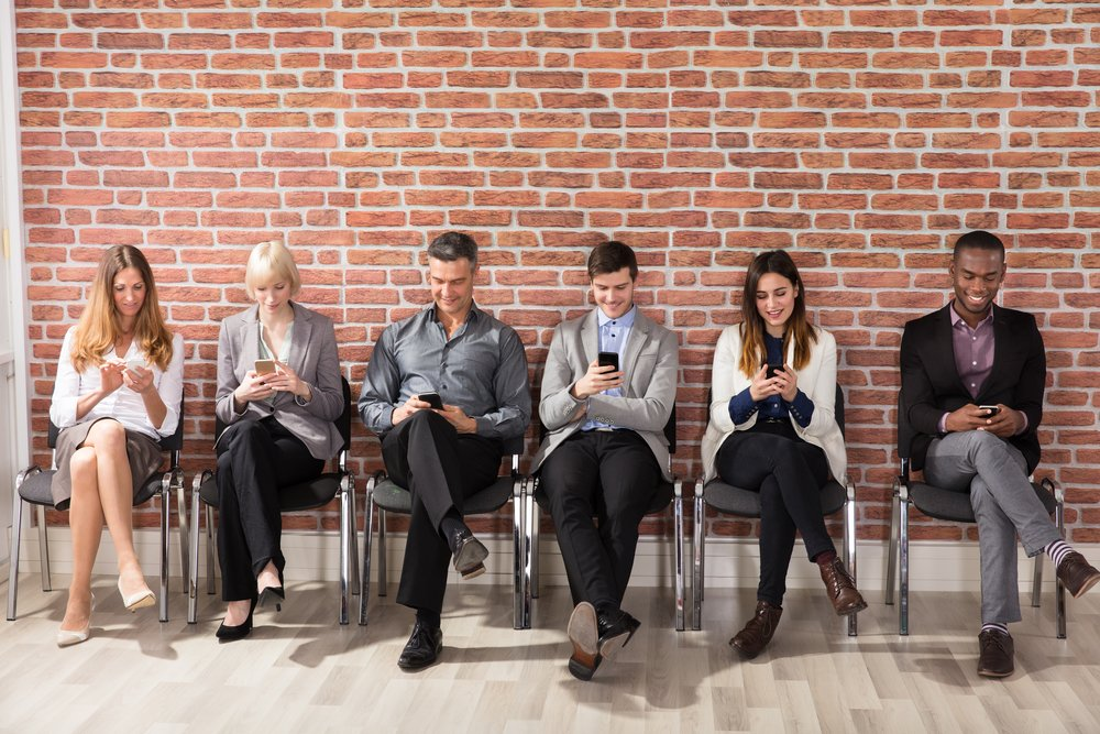 A diverse group of job applicants sitting in a row in front of a red-brick wall