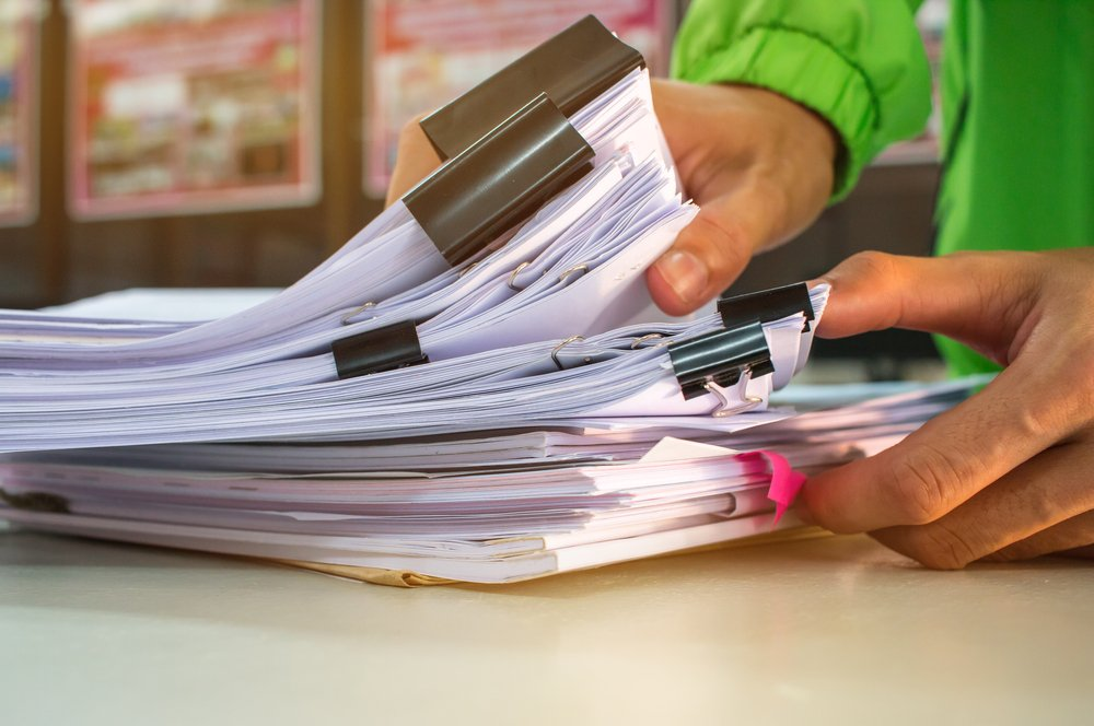 close up of hands sorting through paper forms on work desk