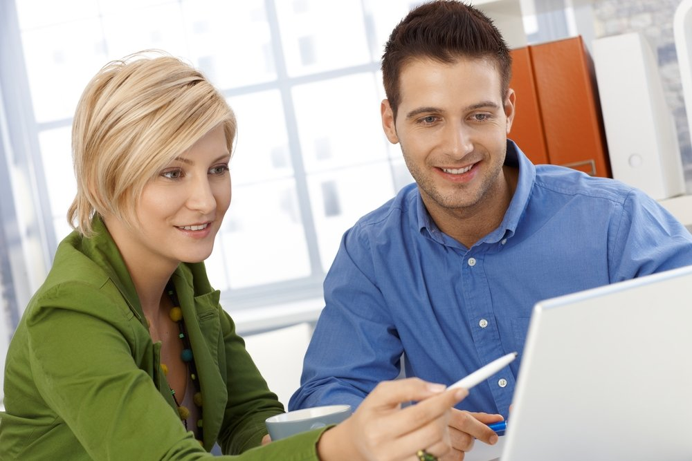 Two young business professionals looking at computer