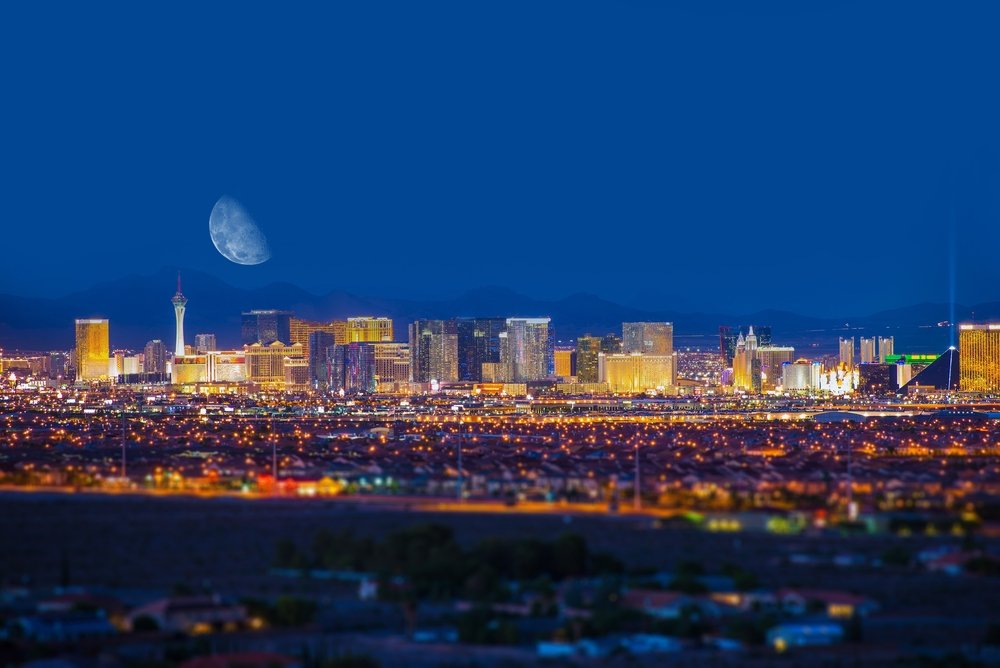 Night photo of Las Vegas skyline with moon over the buildings