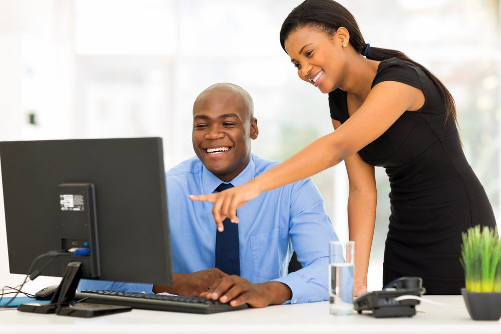 A businessman and businesswoman looking together at a computer in the office