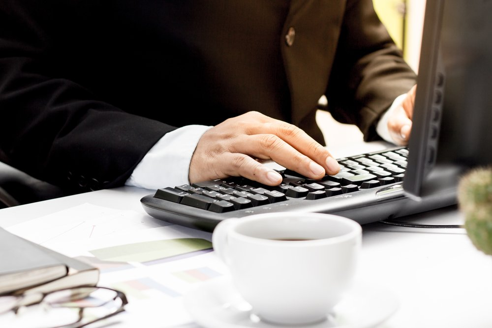 Close of of businessman's hands on computer keyboard working in office