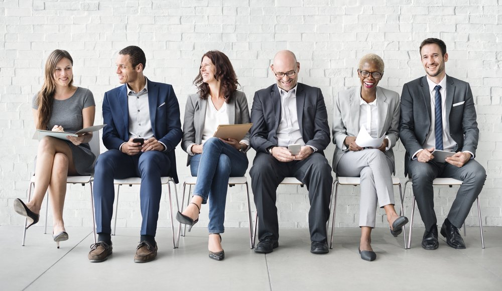 Diverse business people sitting in a row of chairs in front of a whiite brick wall