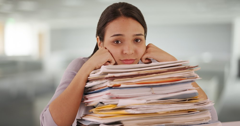 A young business woman resting her chin on a stack of file folders and papers