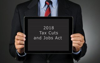"Business man in suit holding sign that reads ""2018 Tax Cuts and Jobs Acti"""