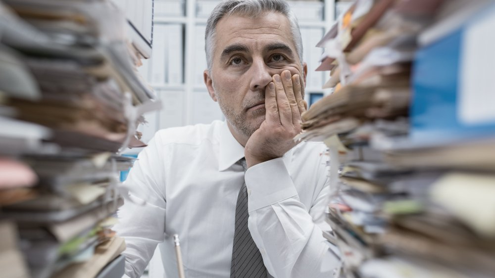 Businessman looking through two tall stacks of paper forms and files