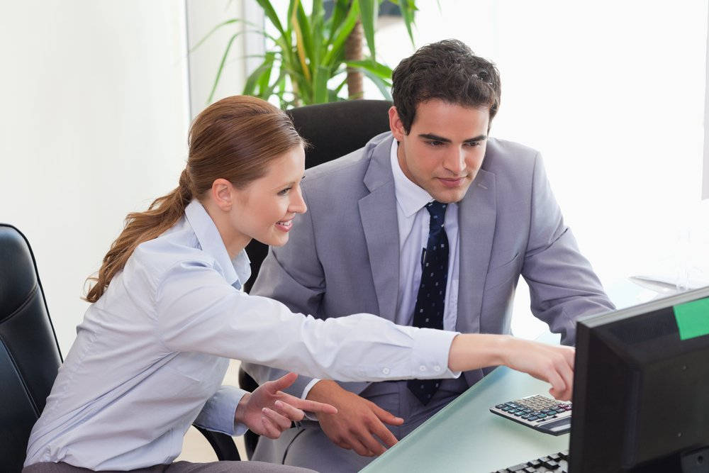 Two business people working at computer on desk in office