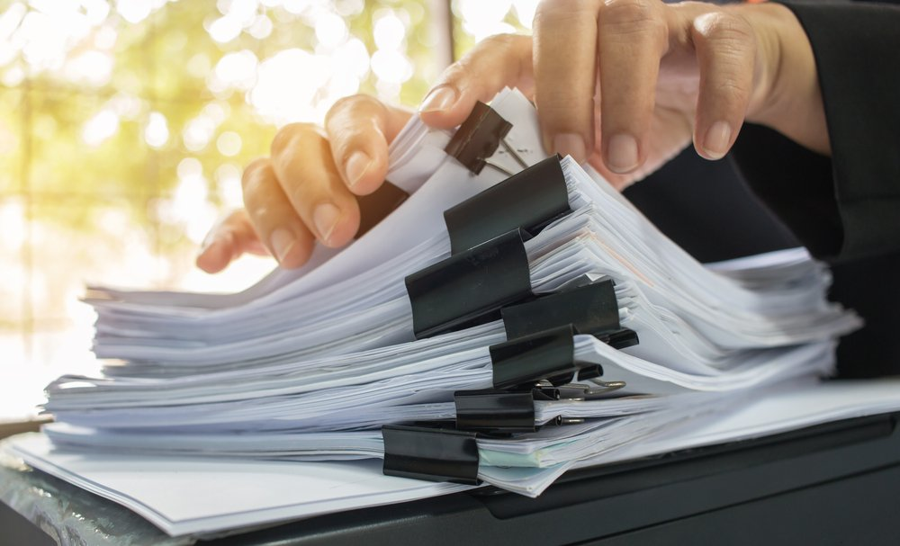 Businessman's hands searching through stack of paper documents on his desk