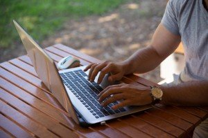 Close up of man outside with hands on laptop keyboard