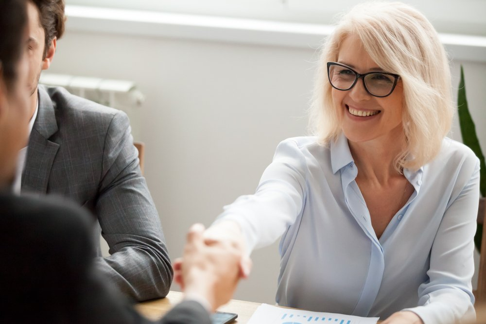 smiling business woman shaking hands with new employee