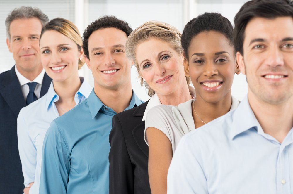 A group of coworkers smiling, standing in a line