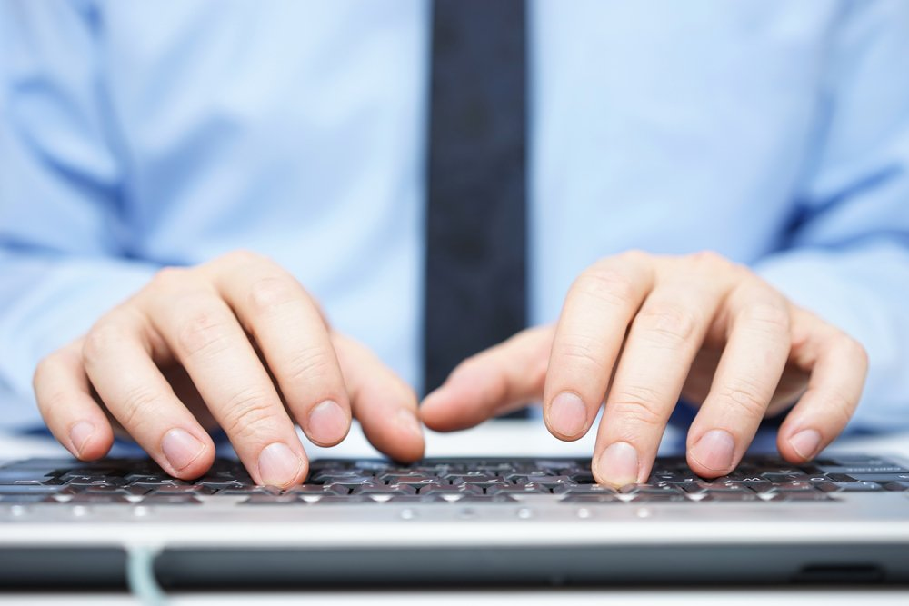Close up of businessman's hands on keyboard at office