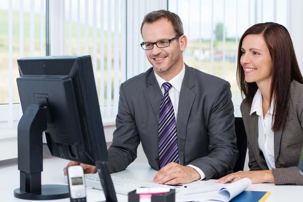 Two business people working at a desktop computer in the office