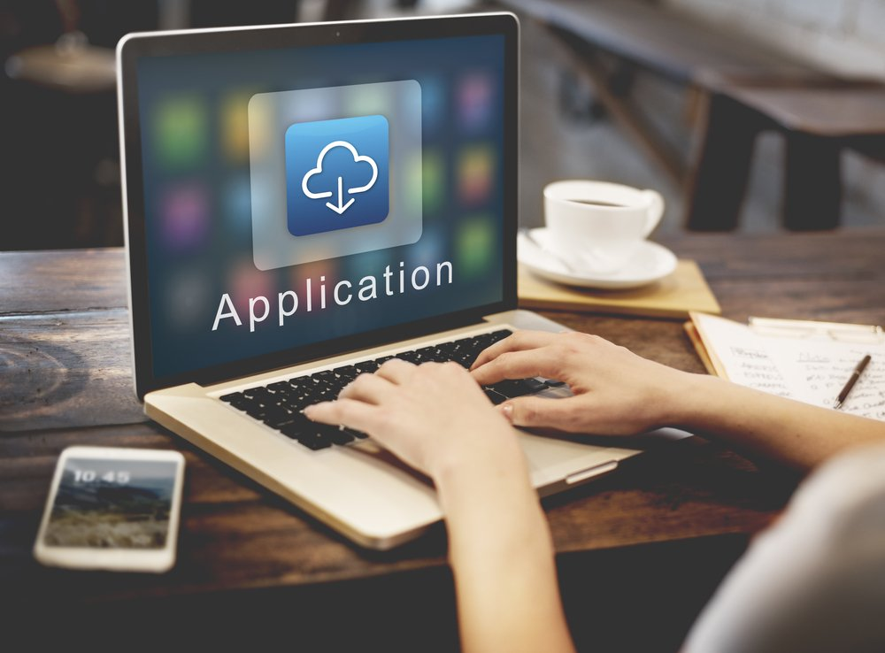 """Close up of person working on laptop on a wooden table. The laptop displays the word """"Application"""" beneath an icon of a cloud with an downward pointing arrow."""