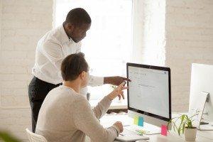 Young businessman mentoring another at his desktop computer