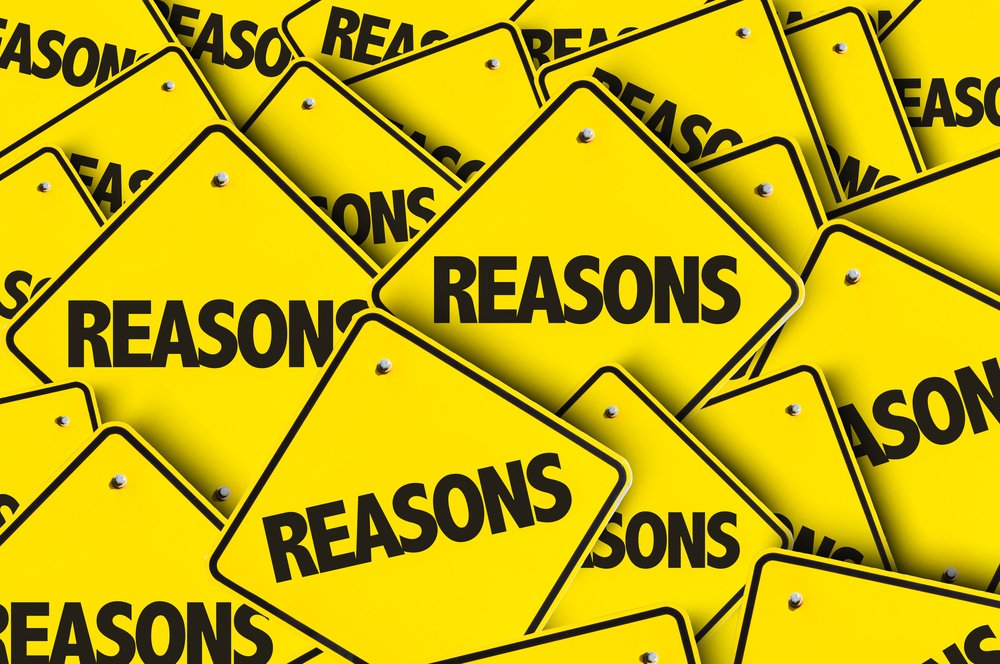 "Lots of diamond shaped yellow signs with the word ""REASONS"" in black on each one"