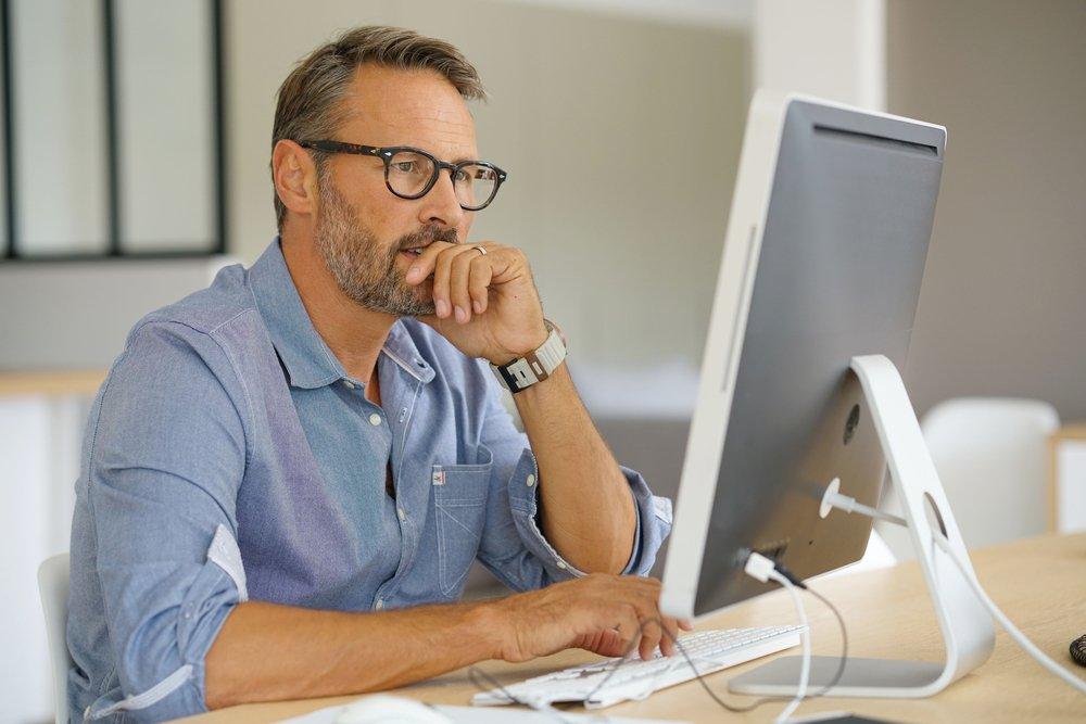 Serous man working at desktop computer