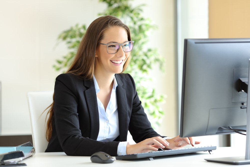 Young business woman smiling while working at her desktop computer in the office.