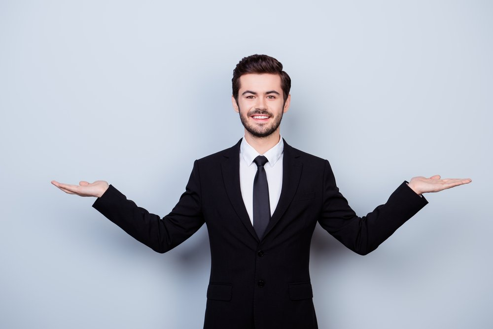 Young business man in suit with palms up weighing options