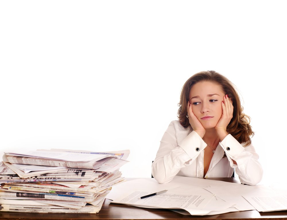 Discouraged businesswoman looking at stack of paperwork