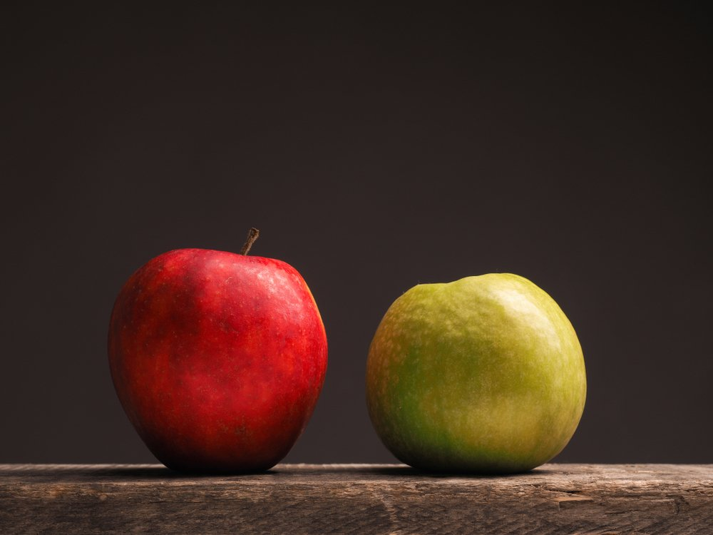 closeup of a red and a green apple sitting on a wooden table