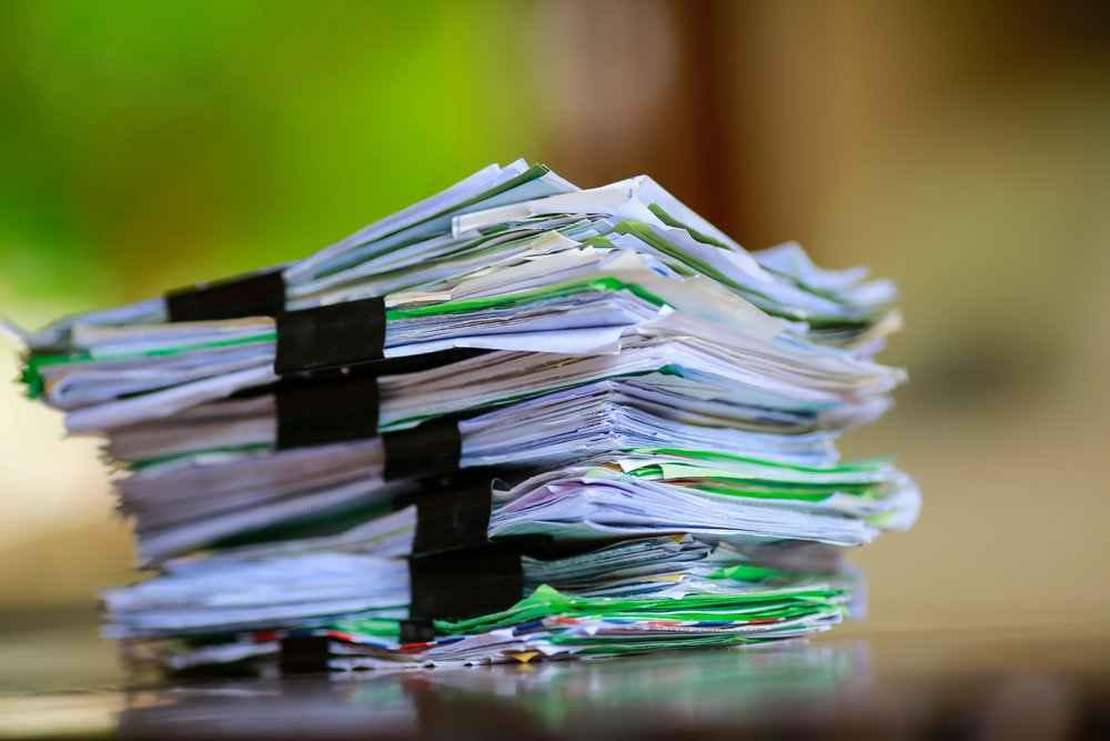 A stack of paper forms on an office desk