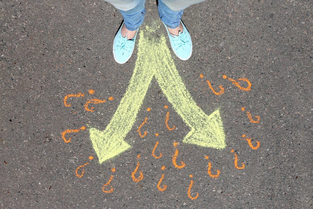 Woman's feet standing on pavement with two arrows and question marks drawn with colored chalk