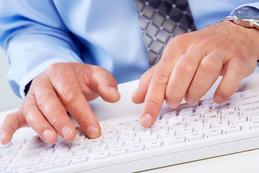 Close up of business man in tie hands on computer keyboard