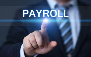"Businessman standing behind virtual screen, touching the point under the word ""Payroll"""